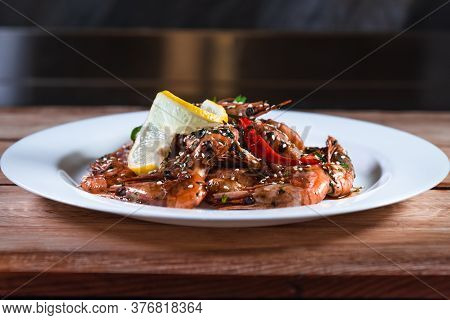 Appetizing Fried Shrimp With Specialties, Sesame Seeds And Lemon, On A White Plate On A Background O