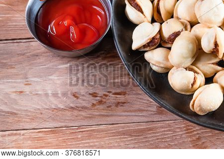 Appetizing Fried Dumplings In A Black Plate On A Wooden Table. Simple Rustic Food And Snacks Concept