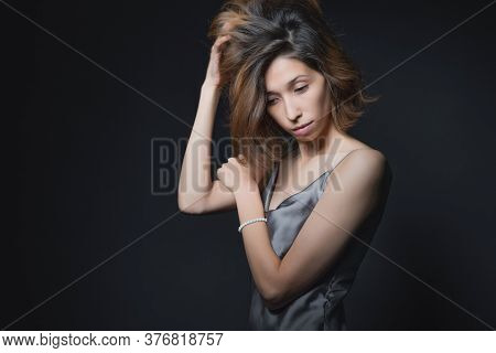 Portrait Of A Beautiful Young Girl On A Dark Background In A Gray Silk Dress. The Concept Of Beauty,