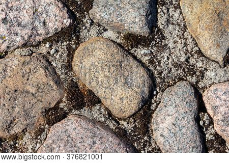 Large Round Stones In A Cement Masonry Wall. Stony Texture Background
