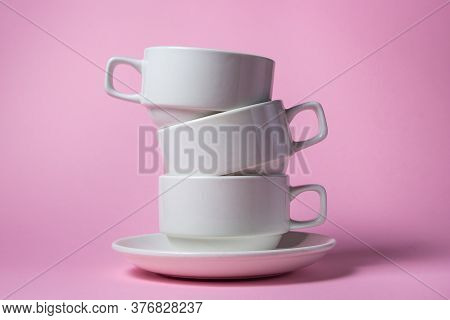 White Cups Stacked On Top Of Each Other On A Pink Background. Three White Porcelain Cups On One Sauc