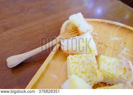 Wood Fork Stabbed On Baked Bread With Butter And Sweetened Condensed Milk In Wooden Plate