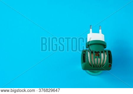 Green Fumigator On A Blue Background Top View. Mosquito Protection Concept.