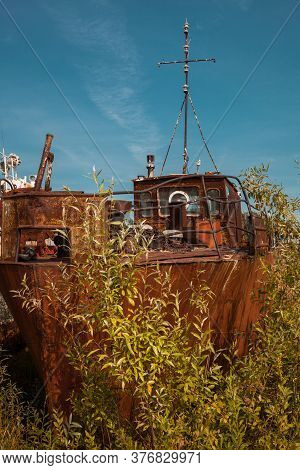 An Old Rusty Broken Ship, Abandoned On The Beach, In The Middle Of A Thicket Of Grass.