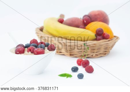 Rolled Oats With Blueberries And Raspberries With Fruit In Wicker Basket. Healthy Breakfast Cereal O
