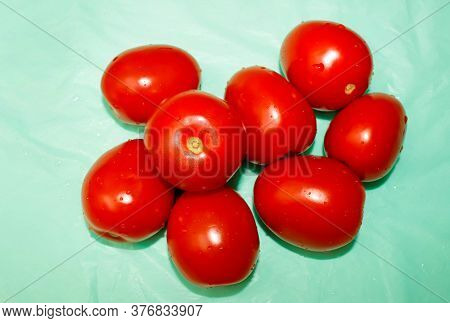 A Few Ripe Red Tomatoes In A Pile On A Blue Background. Selective Focus.