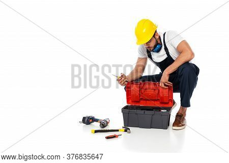 Workman In Hardhat And Ear Defenders Holding Screwdriver Near Tools And Toolbox On White Background