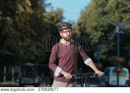 Portrait Of A Male Commuter Wearing Bike Helmet In A Town. Safe Cycling In City, Bicycle Commuting,