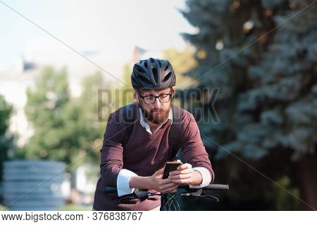 Millennial Bike Commuter In Helmet With A Phone. Safe Cycling In The City, Green Transport, Using Bi
