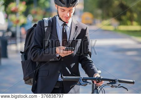 Male Bicycle Commuter In A Suit And Helmet With A Phone. Cycling Around The City, Going To Office Wo