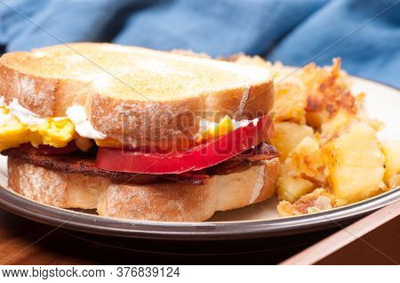 Eggs, Bacon, Tomato And Cheve Cheese Breakfast Sandwich With Pan Fried Potatoes