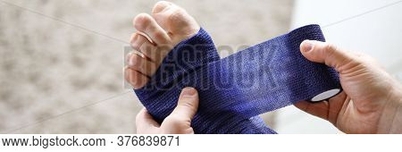 Close-up Of Male Hands Holding Medical Blue Bandage And Bandaging Injured Feet. Consequence Of Accid