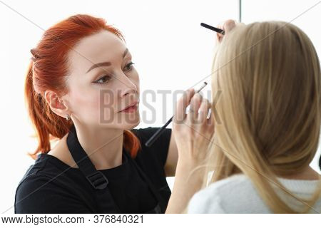 Stylish Makeup Artist Does Makeup On Face Blonde. Art Procedure. Creating Trendy Image For Girl. Adv