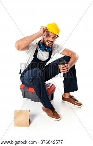 Smiling Workman In Uniform And Hardhat Holding Coffee To Go While Sitting On Toolbox Near Paper Bag