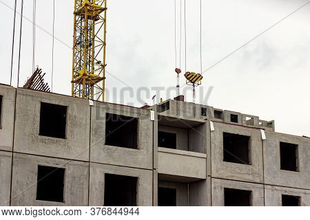 Construction Site With The High Crane Building A Grey Block House In The City.