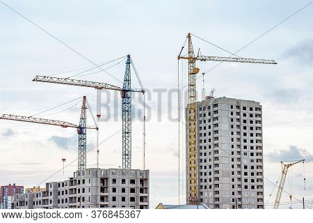 Construction Site With The High Cranes Building A Grey Block House In The City.