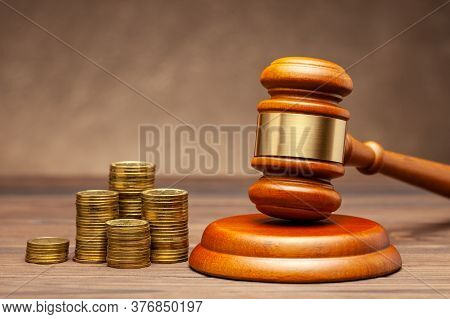 Stack Of Coins And Judge Gavel On Brown Background. The Concept Of Non-payment Of Taxes.