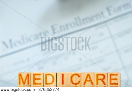 Medicare Concept. Wooden Blocks With The Inscription On The Background With Medicare Enrollment Form