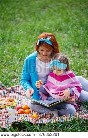 Little Girl Child And Mother Woman Sit On The Bedspread And Read A Book With A Fairy Tale, Green Gra