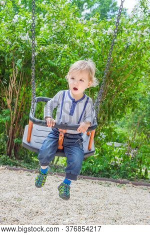 Cute Little Child Having Fun On A Swing In The Park. Beautiful Summer Sunny Day In Children Playgrou