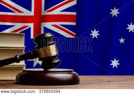 Justice And Court Concept In Commonwealth Of Australia. Judge Hammer On A Flag Background.