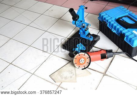 Angle Grinder Stand And Angle Grinder With Circular Saw Blade On The Floor With A Blue Tool Box.