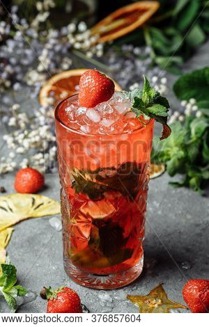 Strawberry Mojito. Cold Summer Mojito Cocktail With Strawberries, Mint, Lemon And Ice In A Glass On
