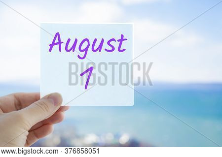 August 1st. Hand Holding Sticker With Text August 1 On The Blurred Background Of The Sea And Sky. Co