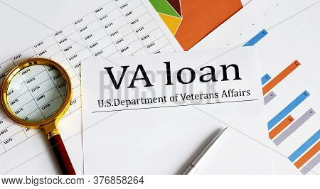 Paper With Va Loan On A Table With Charts, Pen And Magnifier