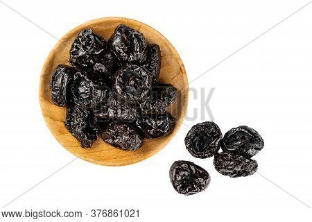 Top View Of Dried Pitted Prunes In Wooden Plate And Prunes On The Floor Over White Background With C