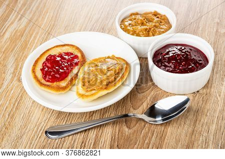 Pancakes With Jam And Peanut Butter In White Saucer, Bowls With Raspberry Jam And Peanut Butter, Tea