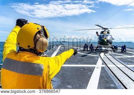 Chonburi, Thailand - July 9, 2020: Flight Deck Officer Directs Seamen Chalk And Chain An Eurocopter