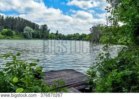 Forest Lake With A Wooden Pier In The Village Of Uhroidy (sumy Region, Ukraine). Beautiful Natural L