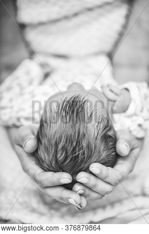 Loving Mom Carying Of Her Newborn Baby At Home. Close Up Photo Of Happy Mum Holding Sleeping Infant