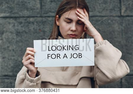 Young Woman Hold White Paper Poster In Hand. Sad Girl With White Blank Template Sheet With Inscripti