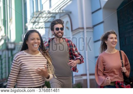 Guy In Sunglasses And Two Girls Running Down Street