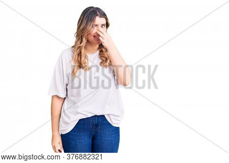Young caucasian woman wearing casual clothes smelling something stinky and disgusting, intolerable smell, holding breath with fingers on nose. bad smell