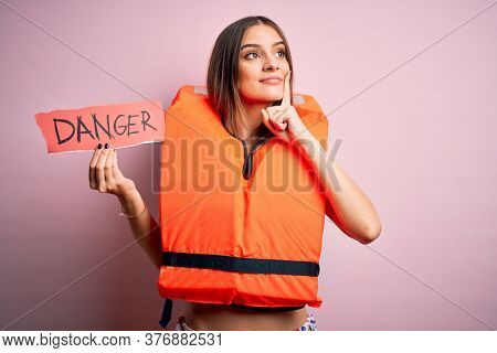 Young beautiful brunette woman wearing lifejacket holding paper with danger message serious face thinking about question, very confused idea