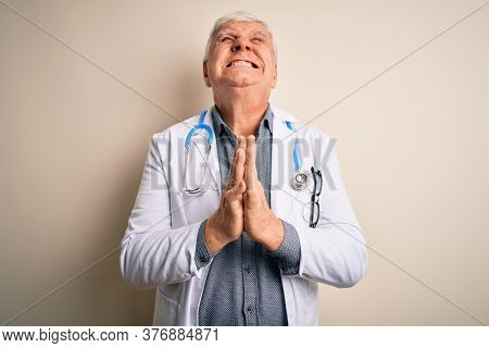 Senior handsome hoary doctor man wearing coat and stethoscope over white background begging and praying with hands together with hope expression on face very emotional and worried. Begging.