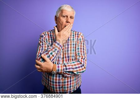 Senior handsome hoary man wearing casual colorful shirt over isolated purple background bored yawning tired covering mouth with hand. Restless and sleepiness.