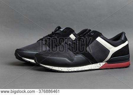 A Pair Of New Black Sneakers On A Dark Gray Background. Comfortable Casual Shoes And Sports Shoes