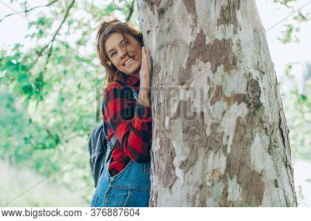 Casual Cheerful Brunette Embracing A Tree. Woman Hugging Tree