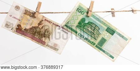 Belarusian Rubles And Russian Rubles Hang On A Rope On A White Background. Money