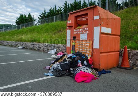 Prestatyn, Wales Uk: Jun 7, 2020: A Charity Clothing Bank Is Overflowing. Excess Donations In Plasti