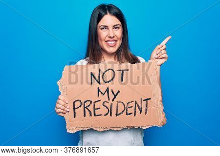 Young beautiful woman on disagreement holding banner with not my president message smiling happy pointing with hand and finger to the side