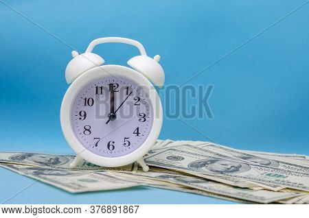 White Alarm Clock Stands On Dollar Bills On A Blue Background. Concept Of Business Planning And Fina