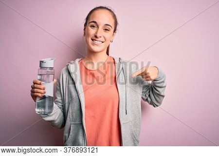 Young beautiful sporty woman doing sport drinking bottle with water to refreshment with surprise face pointing finger to himself