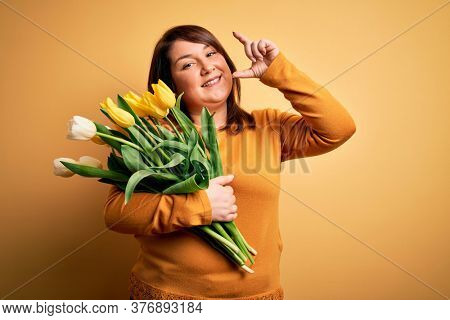 Beautiful plus size woman holding romantic bouquet of natural tulips flowers over yellow background smiling and confident gesturing with hand doing small size sign with fingers looking and the camera