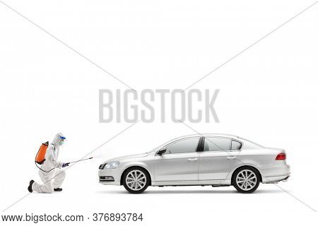 Full length profile shot of a man in a hazmat suit kneeling and disinfecting a car isolated on white background