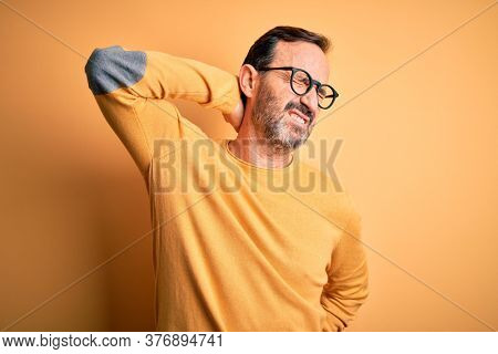 Middle age hoary man wearing casual sweater and glasses over isolated yellow background Suffering of neck ache injury, touching neck with hand, muscular pain